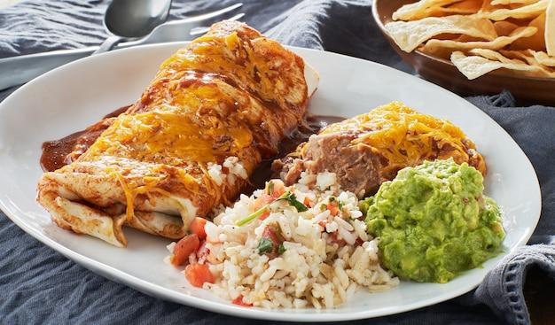 Mexikanische burritoplatte mit roter enchiladasauce, gebratenen bohnen, reis und guacamole