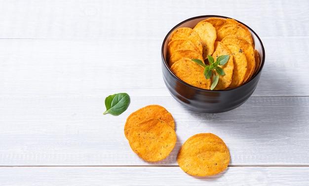 Mexikanische chips nachos in der schwarzen schüssel mit basilikum auf weißem holzhintergrund. draufsicht und kopierraum
