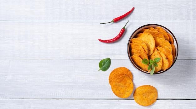 Mexikanische chips nachos in der schwarzen schüssel mit basilikum und chilipfeffer auf weißem holzhintergrund. draufsicht und kopierraum