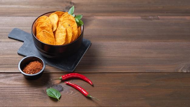 Mexikanische chips nachos in schwarzer schüssel mit paprika und chili-pfeffer auf braunem holzhintergrund. draufsicht und kopierraum