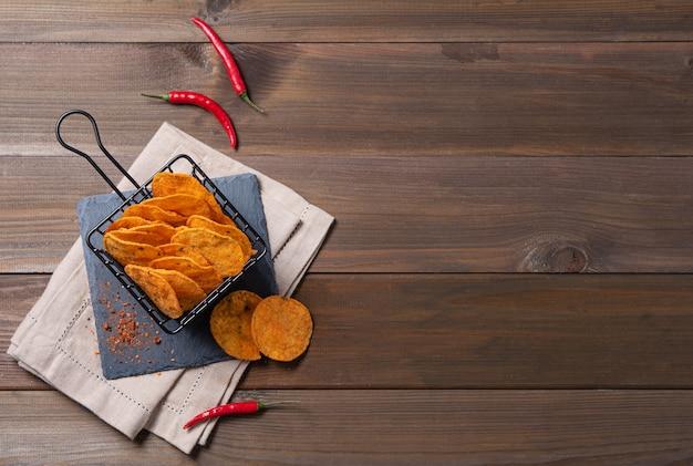 Mexikanische chips nachos mit paprika und chili pfeffer auf braunem holzhintergrund. draufsicht und kopierraum