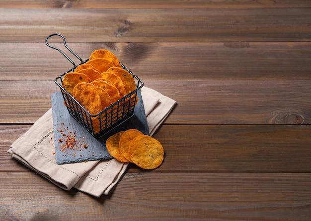 Mexikanische chips nachos mit paprikapfeffer auf braunem holzhintergrund. draufsicht und kopierraum