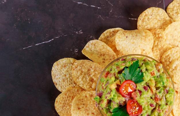 Mexikanische chips und salsa tauchen in glasschüssel ein
