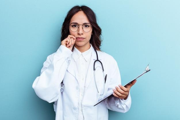 Mexikanische frau des jungen doktors lokalisiert auf blauem hintergrund mit den fingern auf den lippen, die ein geheimnis halten.