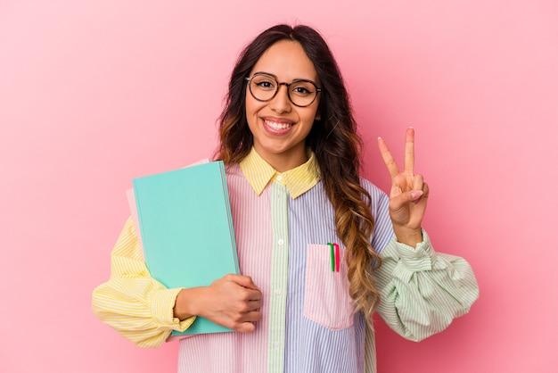 Mexikanische frau des jungen studenten lokalisiert auf rosa hintergrund, der nummer zwei mit den fingern zeigt.
