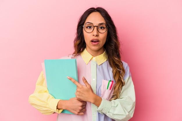 Mexikanische frau des jungen studenten lokalisiert auf rosa hintergrund, der zur seite zeigt