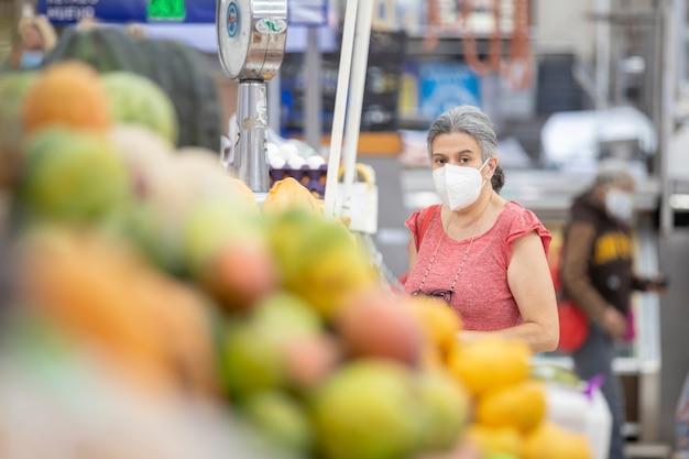 Mexikanische frau, die auf populärem markt in mexiko kauft, trägt gesichtsmaske wegen coronavirus-pandemie