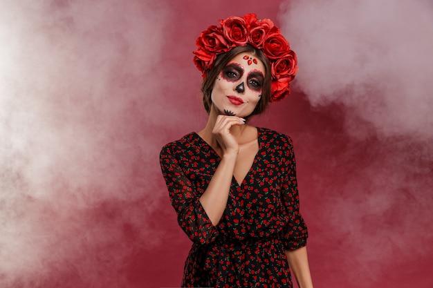 Mexikanische frau in la muerta-kleidung und totenkopf-make-up während halloween mit rauch