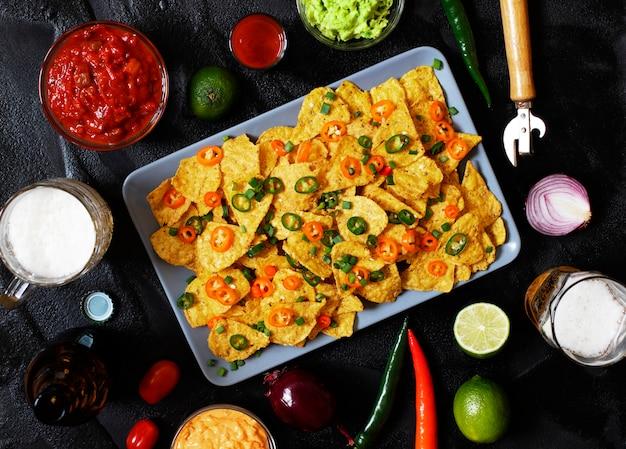 Mexikanische gelbe maistortillachips nachos mit jalapeno, guacamole, käsesoße und salsa. gläser mit bier, limette, chilischoten, kirschtomaten
