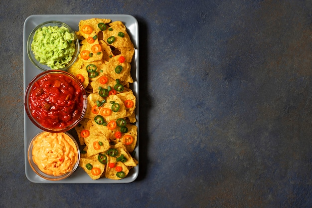 Mexikanische gelbe maistortillachips nachos mit jalapeno, guacamole, käsesoße und salsa