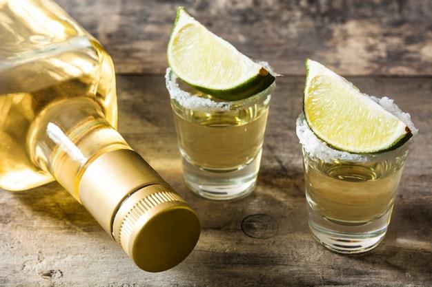 Mexikanische gold tequila flasche und glas mit limette und salz auf holztisch