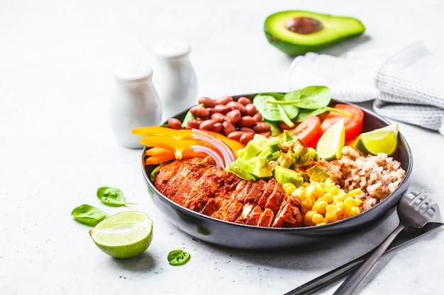 Mexikanische hühnchen-burrito-schüssel mit reis, bohnen, tomate, avocado, mais und spinat, weißer hintergrund. lebensmittelkonzept der mexikanischen küche.