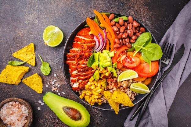 Mexikanische hühnerburritoschüssel mit reis, bohnen, tomate, avocado, mais und spinat. mexikanisches küche-food-konzept.