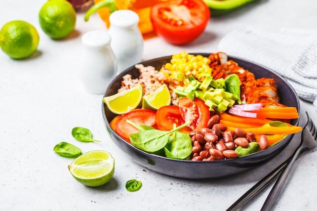 Mexikanische hühnerburritoschüssel mit reis, bohnen, tomate, avocado, mais und spinat.