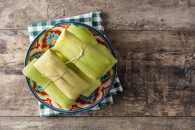Mexikanische mais und huhn tamales auf holztisch
