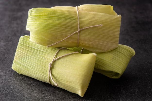 Mexikanische mais und huhn tamales auf schwarzem hintergrund