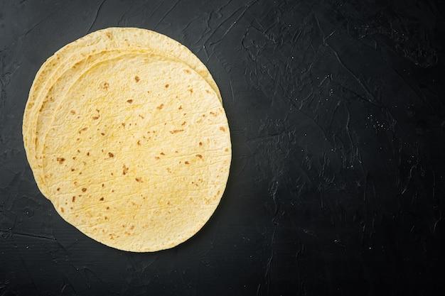 Mexikanische maistortillas, auf schwarzem hintergrund, draufsicht flach mit kopierraum für text