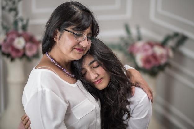 Mexikanische mutter und tochter umarmen sich am muttertag
