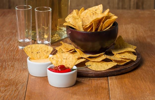 Mexikanische nacho-chips, käse und salsa tauchen in eine schüssel