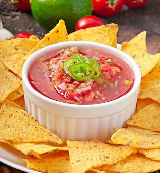 Mexikanische nacho-chips und salsa tauchen in eine schüssel auf holz
