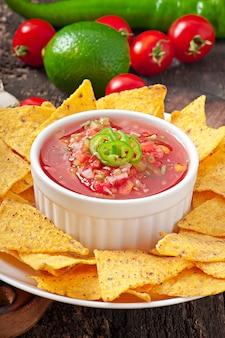 Mexikanische nacho-chips und salsa tauchen in eine schüssel
