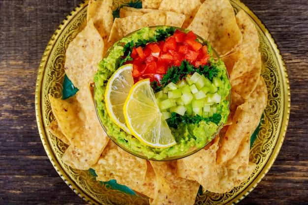 Mexikanische nachochips und guacamole tauchen in schüssel auf hölzernem hintergrund ein