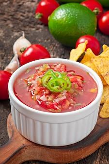 Mexikanische nachochips und salsa tauchen in schüssel auf holzoberfläche ein