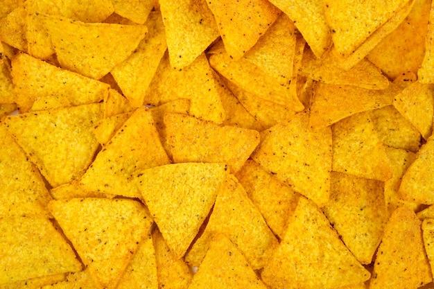 Mexikanische nachos-chips sind über das ganze flugzeug verteilttortilla-chips nachos-snacks tapete draufsicht