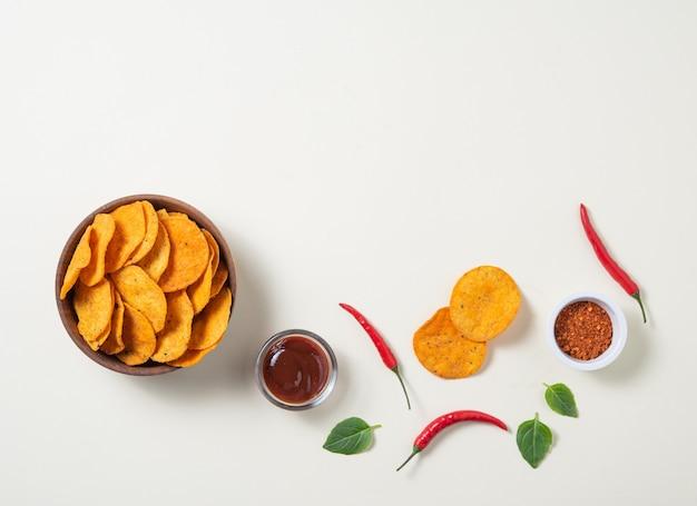 Mexikanische nachos mit chili-pfeffer, gewürzen und grilldip auf gelbem hintergrund. draufsicht und kopierraum
