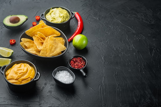 Mexikanische nachos mit soßengarnitur auf schwarzem tisch