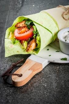 Mexikanische nahrung. gesundes essen. wrap-sandwich: grüne lavash-tortillas mit spinat, gebratenem hähnchen, frischem blattsalat, tomaten, joghurtsauce. dunkler steintisch, marmorplatte.
