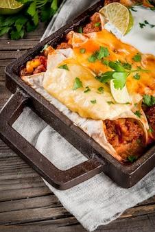 Mexikanische nahrung. südamerikanische küche. traditioneller teller von würzigen rindfleischenchiladas mit mais, bohnen, tomate. auf einem backblech auf altem rustikalem hölzernem hintergrund. kopieren sie platz