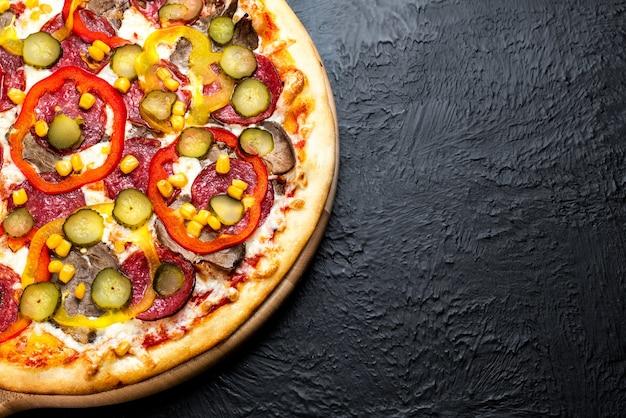 Mexikanische pizza auf schwarzem hintergrund auf tomatenbasis mit mozzarella, salami, rindfleisch, scharfen und süßen paprikaschoten, mais und leicht gesalzener gurke auf einem holzständer