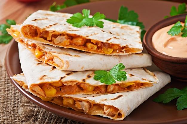 Mexikanische quesadilla in scheiben geschnitten mit gemüse und saucen auf dem tisch