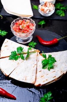 Mexikanische quesadilla mit salsasauce auf schwarzem schiefersteinteller,