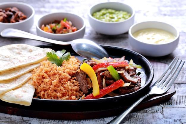 Mexikanische rindfleisch-fajitas, serviert mit reis, tortillas aus weichem mehl auf einer heißen platte und vier verschiedenen saucen