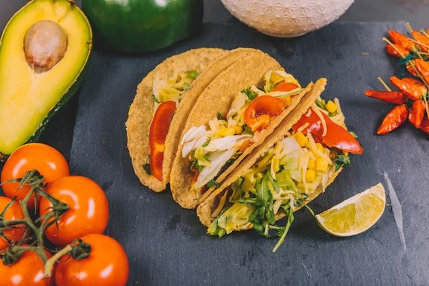 Mexikanische rindfleisch-tacos mit gemüse; tomate; avocado auf schwarzem schiefer