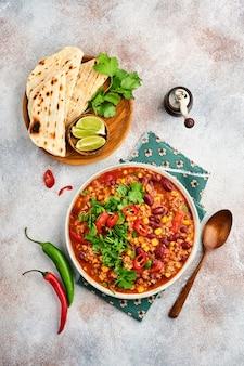 Mexikanische schwarze bohnensuppe mit hackfleisch, tomate, koriander, avocado und gemüseeintopf auf hellgrauem schiefer-, stein- oder betonhintergrund. traditionelles mexikanisches gericht. draufsicht mit kopienraum.