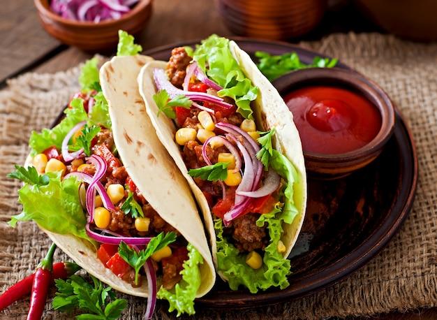 Mexikanische tacos mit fleisch, gemüse und roter zwiebel