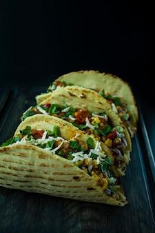 Mexikanische tacos mit fleisch, käse, mais, zwiebeln und schweinefleisch kräutern auf einem holzbrett