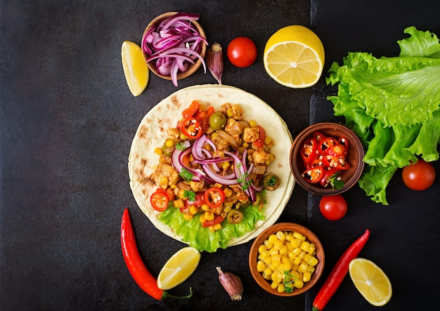 Mexikanische tacos mit fleisch, mais und oliven auf dunklem hintergrund. ansicht von oben