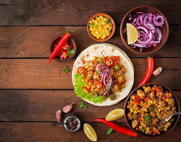 Mexikanische tacos mit fleisch, mais und oliven auf hölzernem hintergrund. ansicht von oben