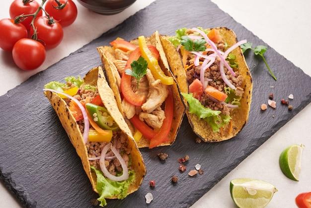 Mexikanische tacos mit fleisch, schweinefleisch carnitas street tacos in gelber maistortilla mit zwiebeln, koriander und kohl. rotkohl. draufsicht. flach liegen.