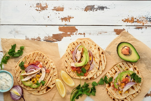 Mexikanische tacos mit gegrilltem huhn, avocado, maiskörnern, tomaten, zwiebeln, koriander und salsa alter weißer holztisch. traditionelles mexikanisches und lateinamerikanisches streetfood. ansicht von oben.