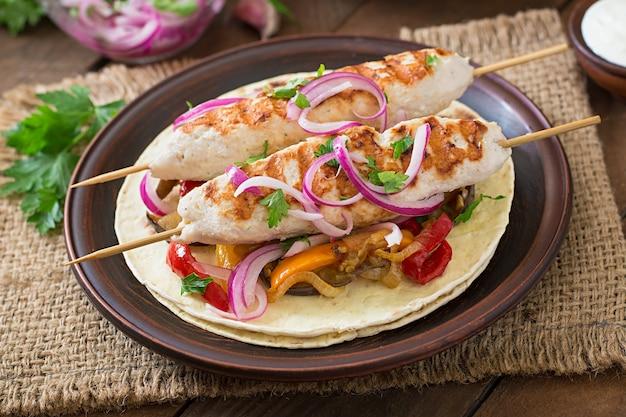 Mexikanische tacos mit hühnchen, gegrilltem gemüse und roten zwiebeln.