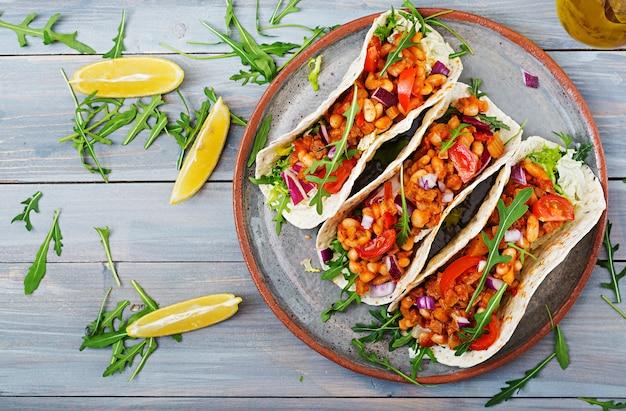 Mexikanische tacos mit rindfleisch, bohnen in tomatensauce und salsa. draufsicht.