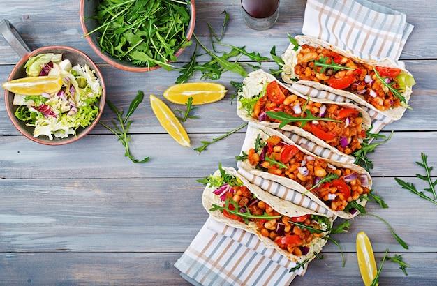 Mexikanische tacos mit rindfleisch, bohnen in tomatensauce und salsa. flach legen.