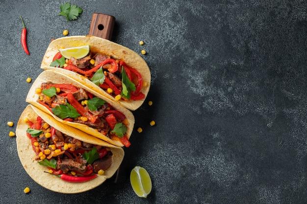 Mexikanische tacos mit rindfleisch, gemüse und salsa.