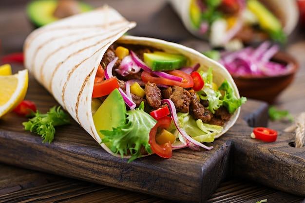 Mexikanische tacos mit rindfleisch in tomatensauce und avocado-salsa