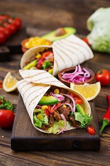 Mexikanische tacos mit rindfleisch in tomatensauce und avocadosalsa